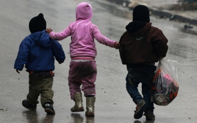 Children walk together as they flee deeper into the remaining rebel-held areas of Aleppo