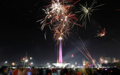 People watch fireworks explode around the National Monument during New Year's Eve celebrations in Jakarta