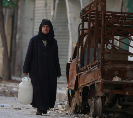 A Woman Carries A Container Of Water As She Walks Past A Burnt Pick-Up Truck In The Rebel Held Area Of Old Aleppo