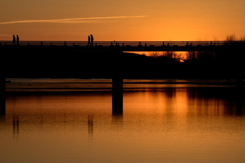 People Cross A Bridge At Sunset In An Encampment During A Protest Against Plans To Pass The Dakota Access Pipeline Near The Standing Rock Indian Reservation, Near Cannon Ball, North Dakota, U.s.