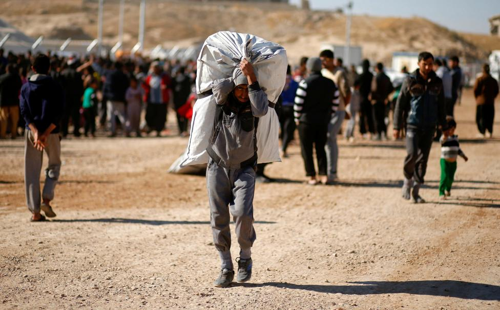 Displaced Iraqi Man Carries A Bag Of Aid He Received At Distribution Point In Khazer Camp