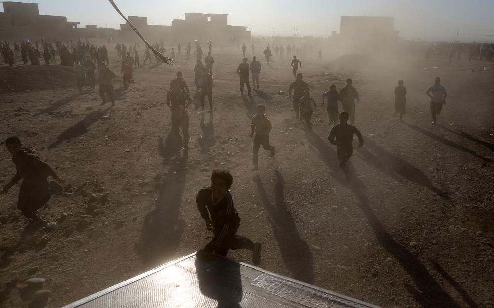 People Run After A Truck Carrying Food Donated By An Iraqi Government Organisation At The Outskirts Of Mosul