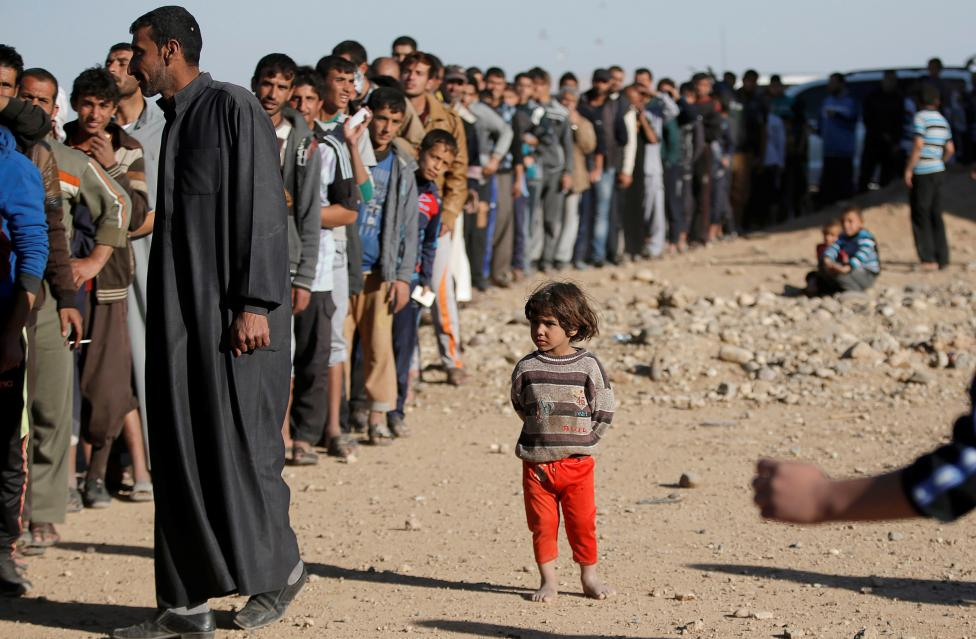 A Child Stands Next To Men Who Are Waiting In Line For Food Donated By An Iraqi Government Organisation At The Outskirts Of Mosul
