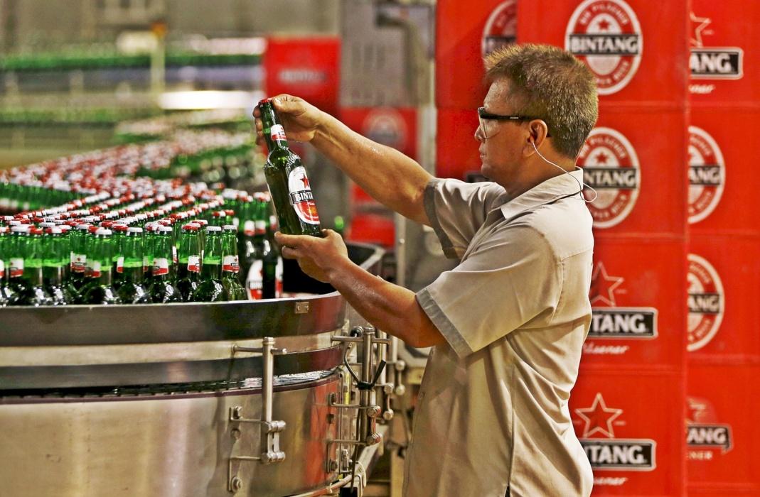 Photo Credit: Pekerja PT Multi Bintang Indonesia Tbk. memegang sebotol bir Bintang untuk memeriksa kualitas di sebuah pabrik bir di Jakarta 17 April 2015. REUTERS