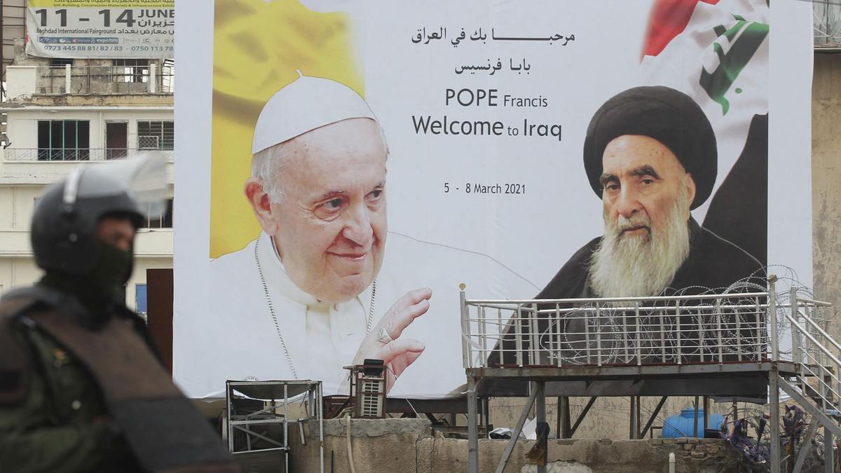 Seorang penjaga keamanan Irak berdiri di depan papan reklame besar bergambar Paus Francis dan Ayatollah Ali Al Sistani, yang bertemu di Najaf, Irak, pada 6 Maret 2021. AFP