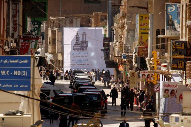 """Sebuah spanduk di Najaf menyambut pertemuan itu """"antara minaret dan lonceng"""". REUTERS"""